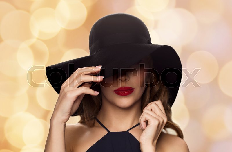 Stock image of 'people, luxury and fashion concept - beautiful woman in black hat over holidays lights background'