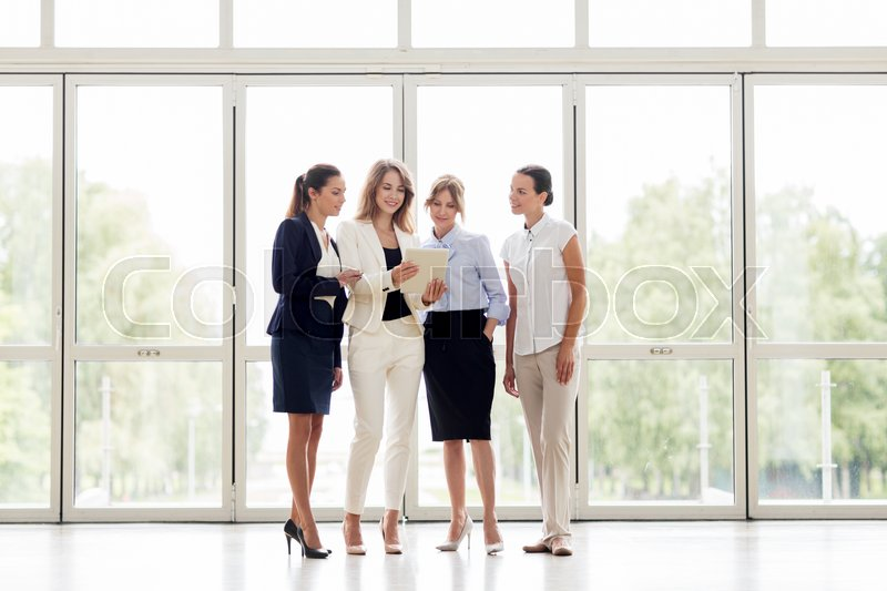 Stock image of 'people, technology, work and corporate concept - business team of women with tablet pc computer at office'