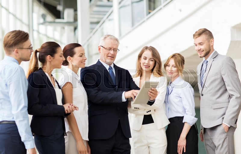 Stock image of 'people, technology, work and corporate concept - business team with tablet pc computer at office'