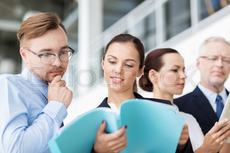 Stock image of 'people, work and corporate concept - business team with folders meeting at office'