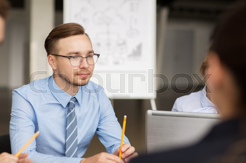 Stock image of 'business, people and technology concept - business team with laptop computer meeting in office'