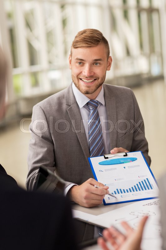 Stock image of 'business, people and statistics concept - happy smiling young businessman with graph on clipboard meeting with colleague at office'