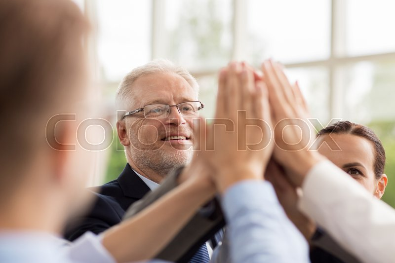 Stock image of 'business, people and teamwork concept - smiling business people making high five in office'