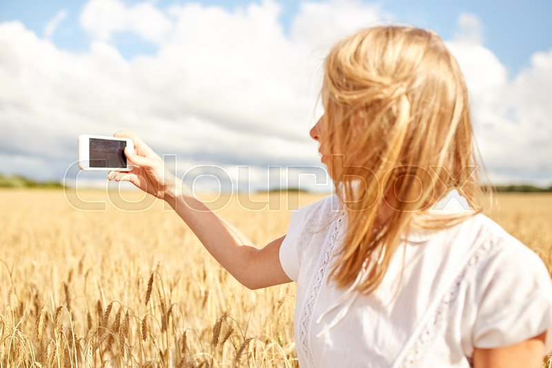 Stock image of 'nature, summer vacation, technology and people concept - close up of young woman with smartphone taking picture of cereal field'