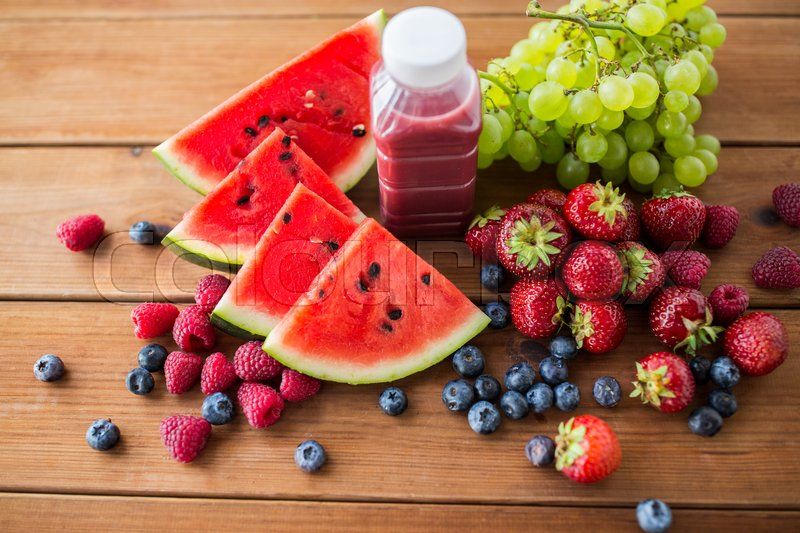 Stock image of 'healthy eating, food, dieting and vegetarian concept - bottle with fruit and berry juice or smoothie on wooden table'