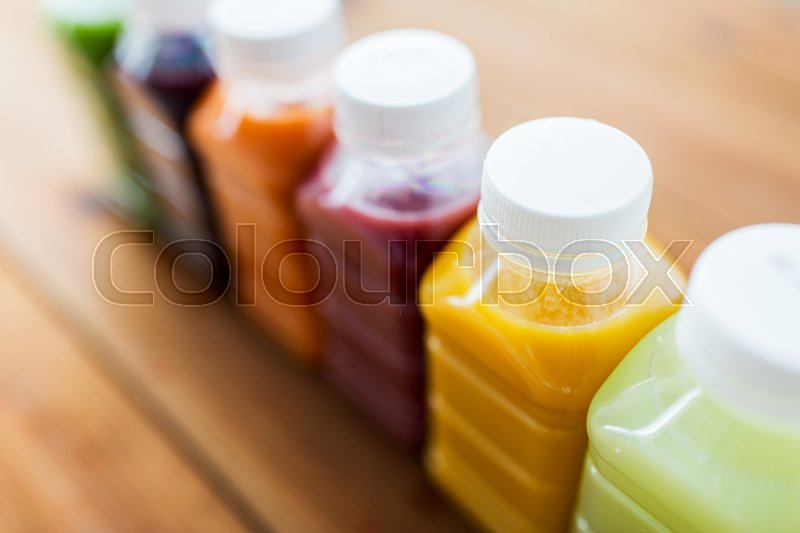 Stock image of 'healthy eating, drinks, dieting and packaging concept - close up of plastic bottles with different fruit or vegetable juices on wooden table'