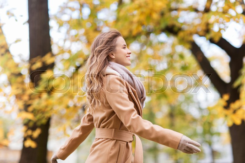 Stock image of 'season and people concept - beautiful happy young woman walking in autumn park'