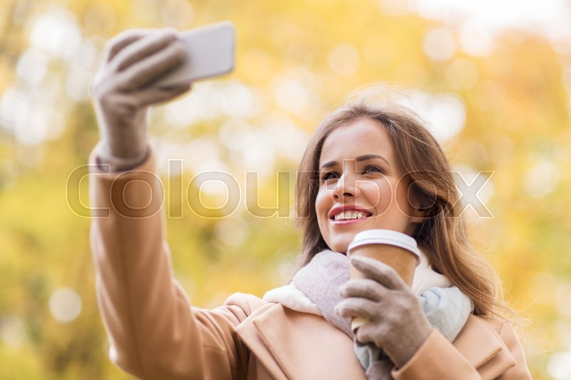 Stock image of 'season, technology and people concept - beautiful young happy woman taking selfie with smartphone in autumn park'