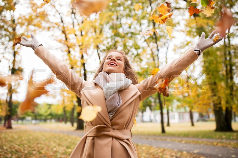 Stock image of 'season and people concept - beautiful happy young woman having fun with leaves in autumn park'