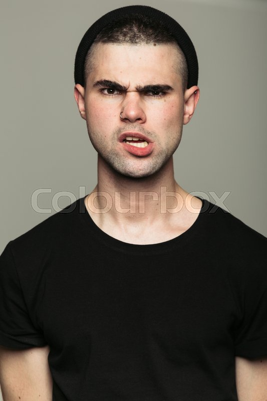 Stock image of 'Studio portrait of provocative angry young man looking at camera on gray background.'
