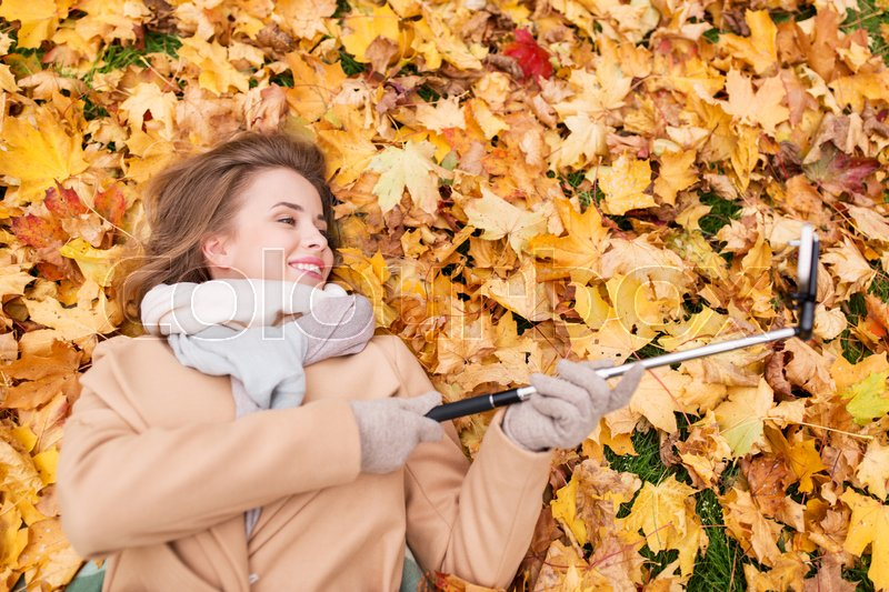 Stock image of 'season, technology and people concept - beautiful young woman lying on ground and autumn leaves and taking picture with smartphone selfie stick'
