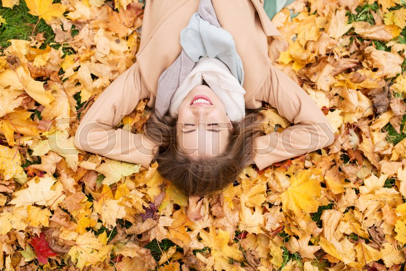 Stock image of 'season and people concept - beautiful young woman lying on ground and autumn leaves'