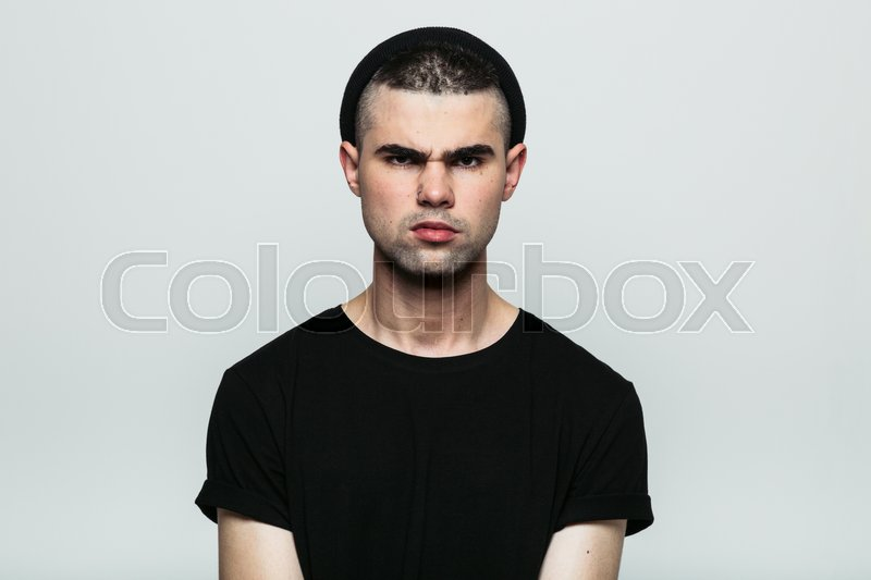 Stock image of 'Studio portrait of aggressive angry young man looking at camera on gray background.'