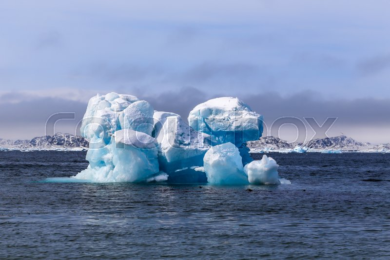 Stock image of 'Huge drifting iceberg, view from old harbor in Nuuk city, Greenland'