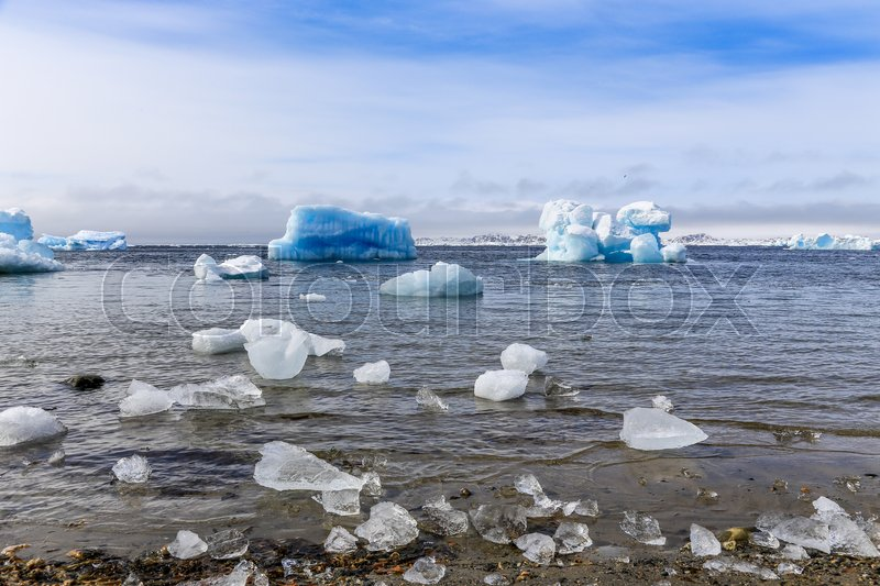 Stock image of 'Huge blue icebergs drifting along the fjord, view from old harbor in Nuuk city, Greenland'