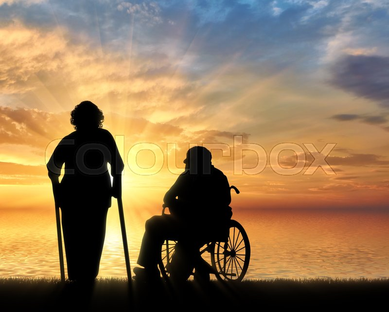 Stock image of 'Silhouette of an old woman on crutches and elderly man in a wheelchair on a background of sea sunset. Concept of disability and old age'