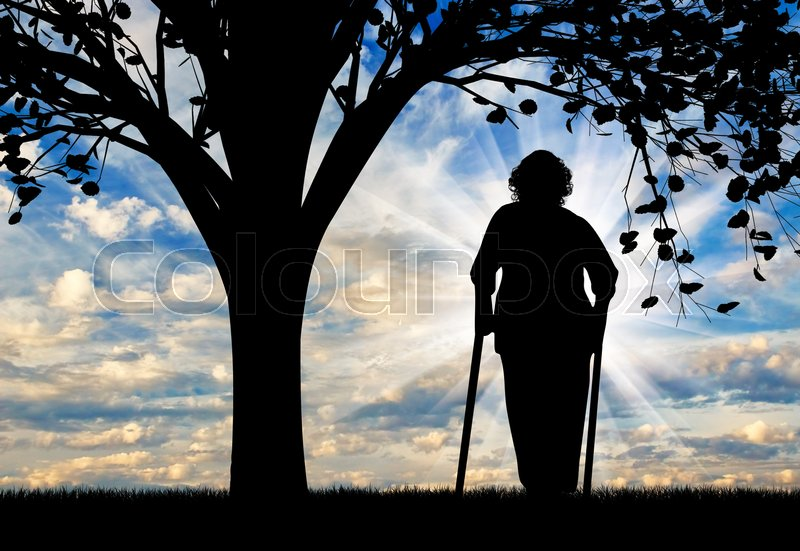Stock image of 'Silhouette of an old woman on crutches resting under a tree. Concept of disability and old age'