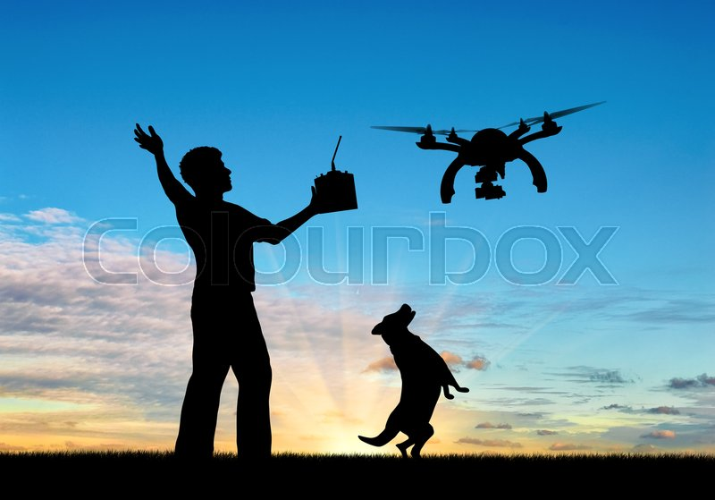 Stock image of 'Silhouette of a flying drone, and a man with a remote control and dog at sunset. Concept quadrocopters'