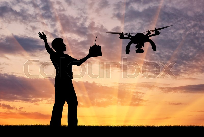 Stock image of 'Silhouette of a flying drone, and a man with a remote control at sunset. Concept quadrocopters'