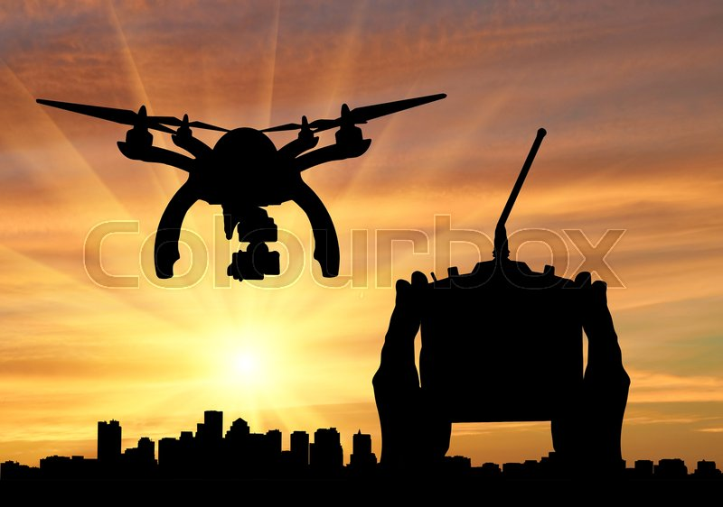 Stock image of 'Silhouette flying reconnaissance drone over city and hand remote control. Concept of military intelligence and information'