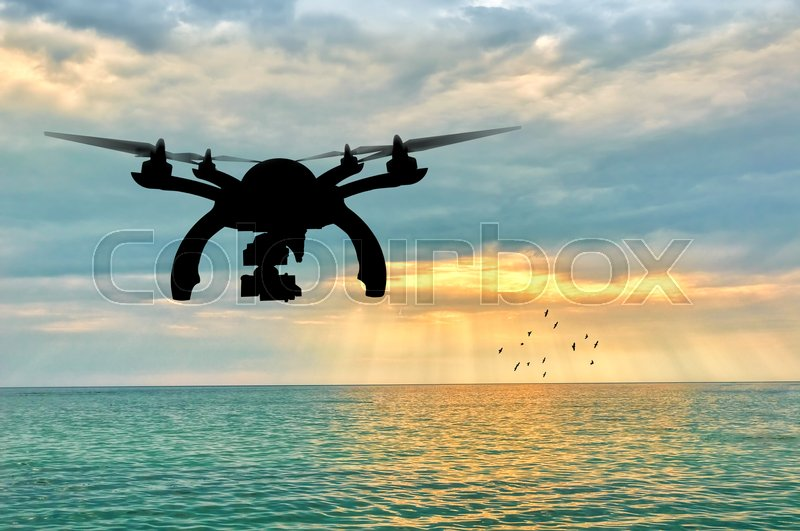 Stock image of 'Silhouette of a flying drone on a background of sea sunset'