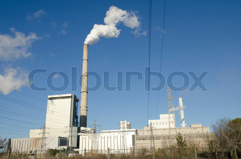 Stock image of 'Industrial production site with a smoking chimney'