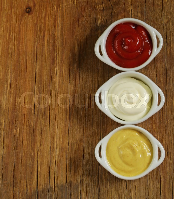 Stock image of 'Mustard, ketchup and mayonnaise - three kinds of sauces'