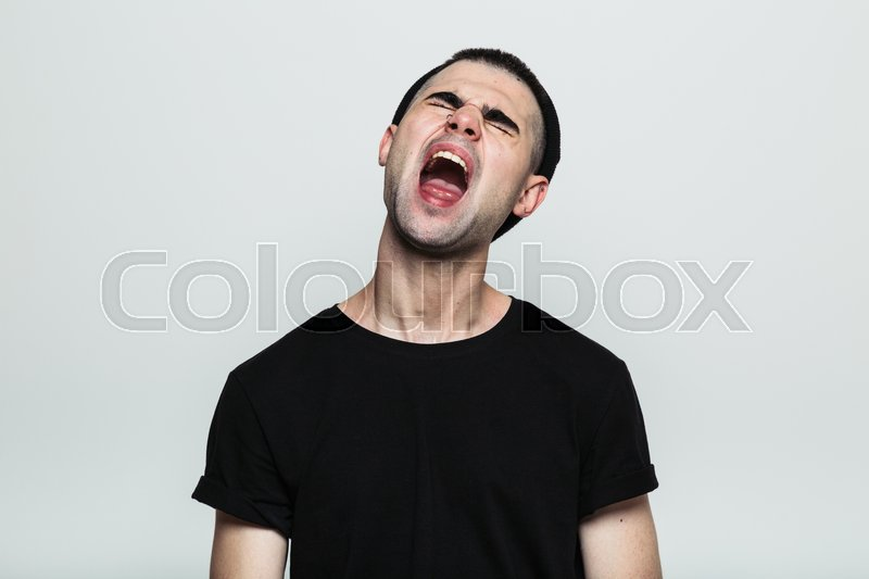 Stock image of 'Studio shot of an annoyed man screaming, his head tilted back'
