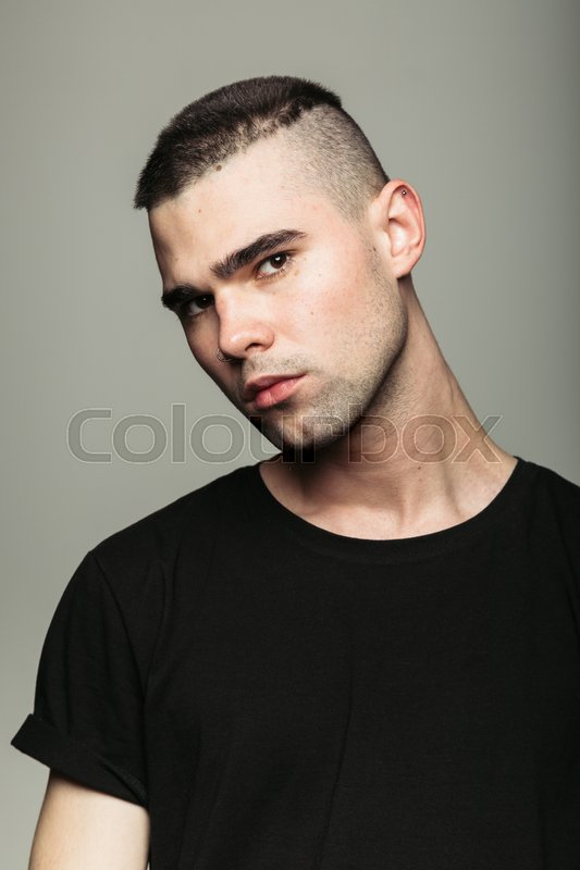 Stock image of 'Close up of brutal handsome guy posing and looking at camera against grey background.'
