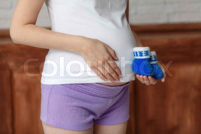 Stock image of 'Pregnant woman holding blue baby booties on belly, close-up'