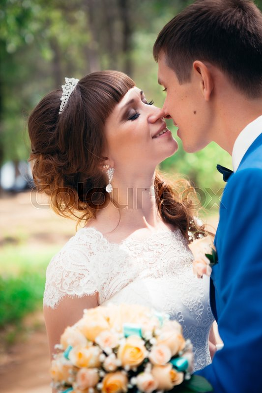 Stock image of 'young bride and groom kissing on the background of the forest and the road.'