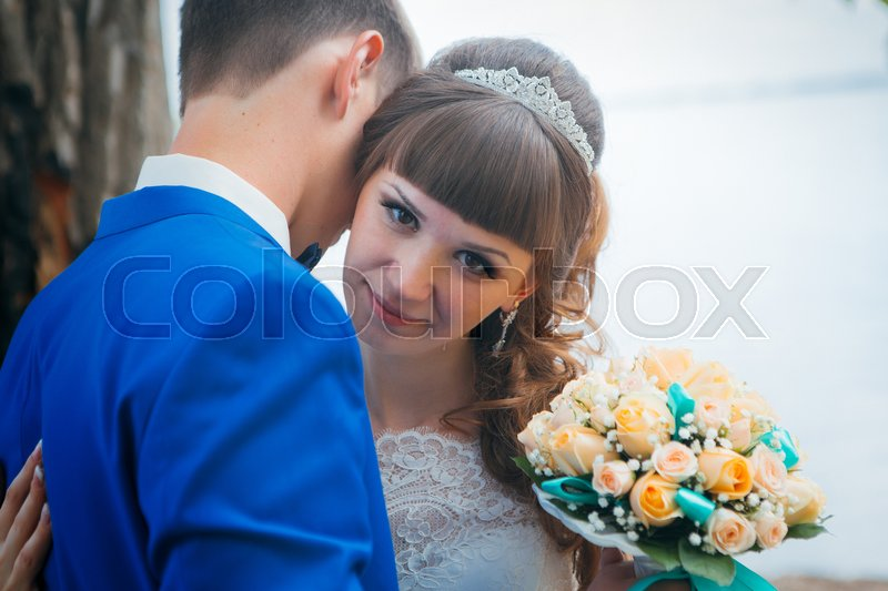 Stock image of 'bride and groom kissing on the background of trees.'