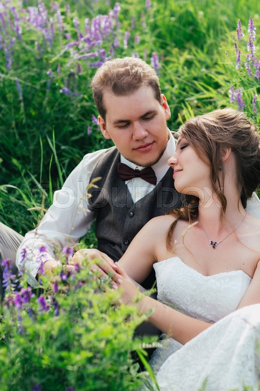 Stock image of 'portrait of the bride and groom resting on a lavender background.'