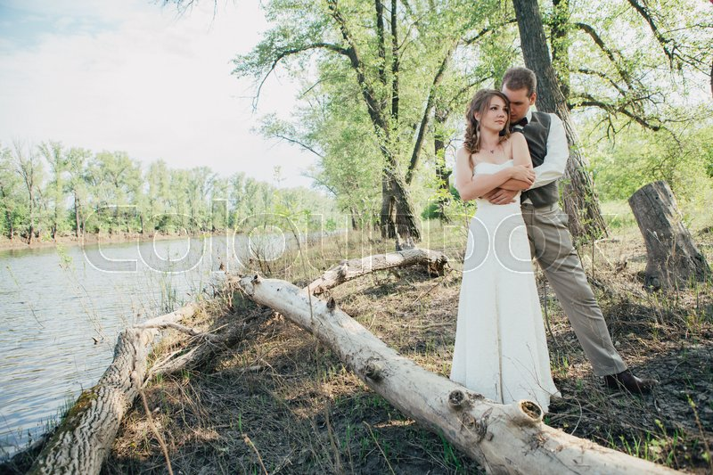Stock image of 'bride and groom standing arm in arm against the background grass and lakes.'