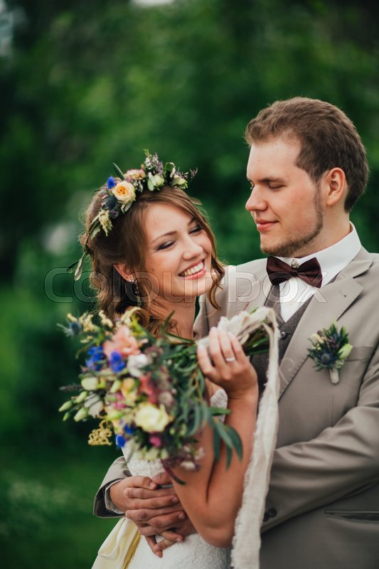 Stock image of 'Young happy bride and groom on the background of greenery.'