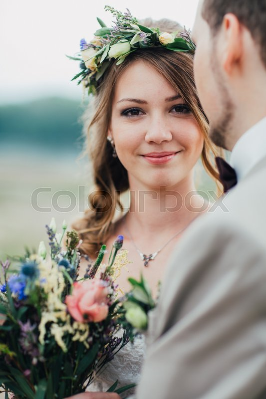 Stock image of 'young groom and bride standing and hugging on the background of the river.'