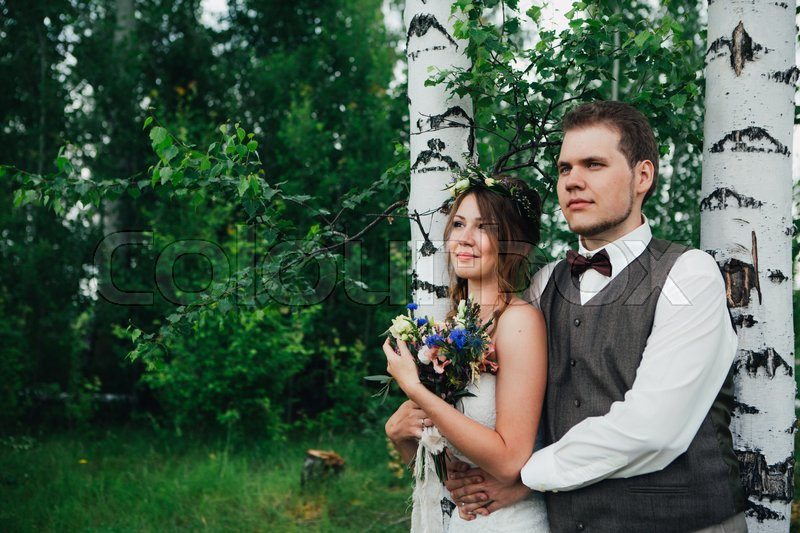 Stock image of 'portrait of a bride and groom embrace on a background of leaves and forest.'