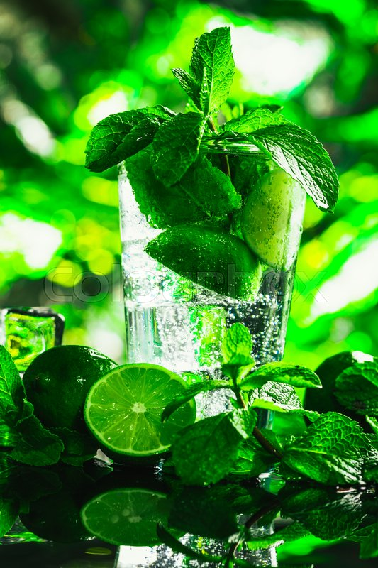 Stock image of 'glass of mojito with lime and mint close-up ice cube on a dark background.'
