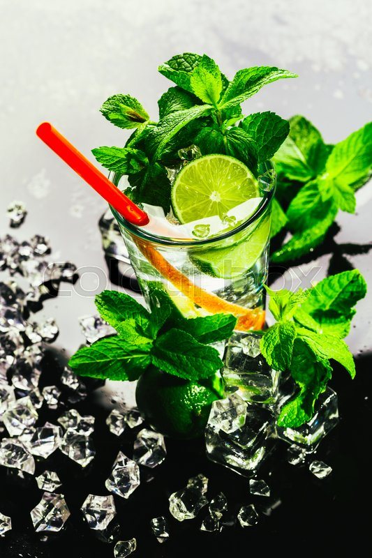 Stock image of 'glass of mojito with lime and mint ice cube close-up with red straw.'