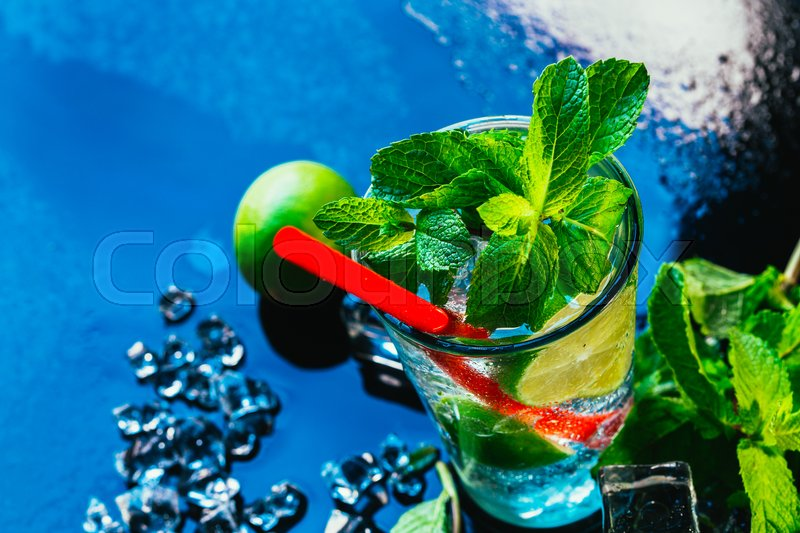 Stock image of 'glass of mojito with lime and mint ice cube close-up with red straw on blue background.'