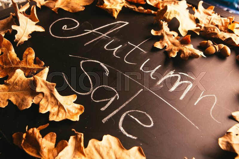 Stock image of 'yellow leaves and the inscription autumn on a blackboard.'