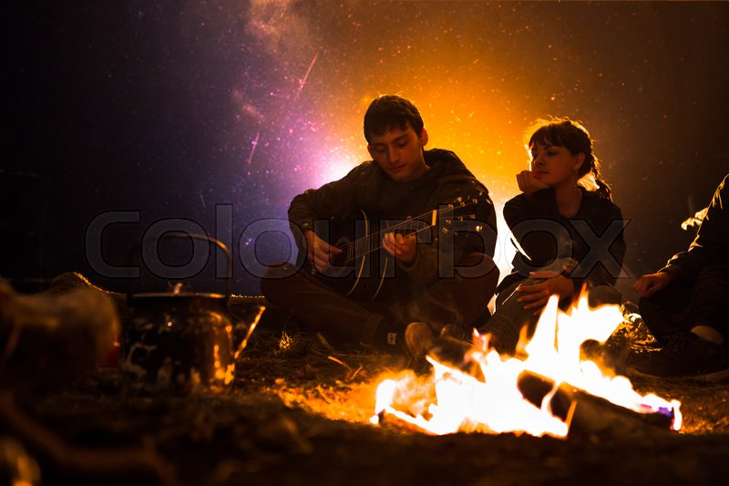 Stock image of 'man plays guitar and woman about the fire on the background of the starry sky.'