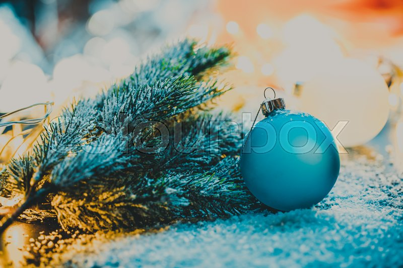 Stock image of 'Blue Christmas tree ball next to the Christmas tree branch.'