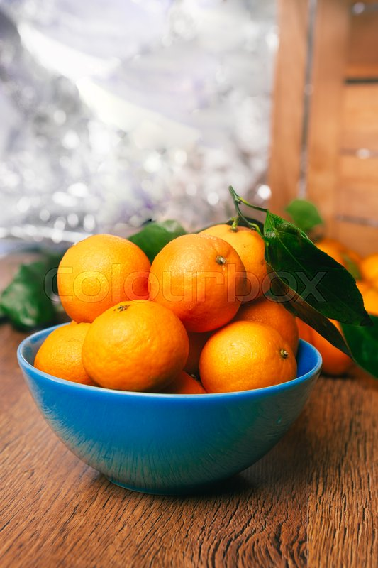 Many fresh mandarin oranges in a blue bowl, standing on a wooden table on a blurred background, stock photo