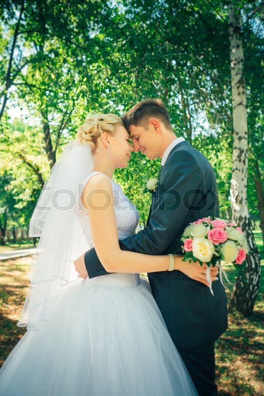 Stock image of 'portrait the bride and groom on the background of the park alley.'