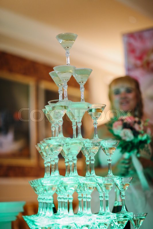Stock image of 'Tower of wine glasses on blurred background.'
