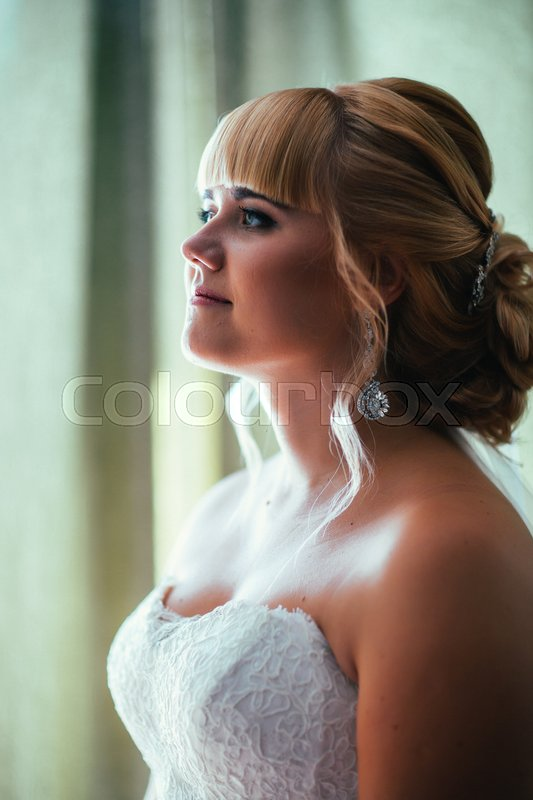 Stock image of 'portrait of young beautiful happy bride near the window.'