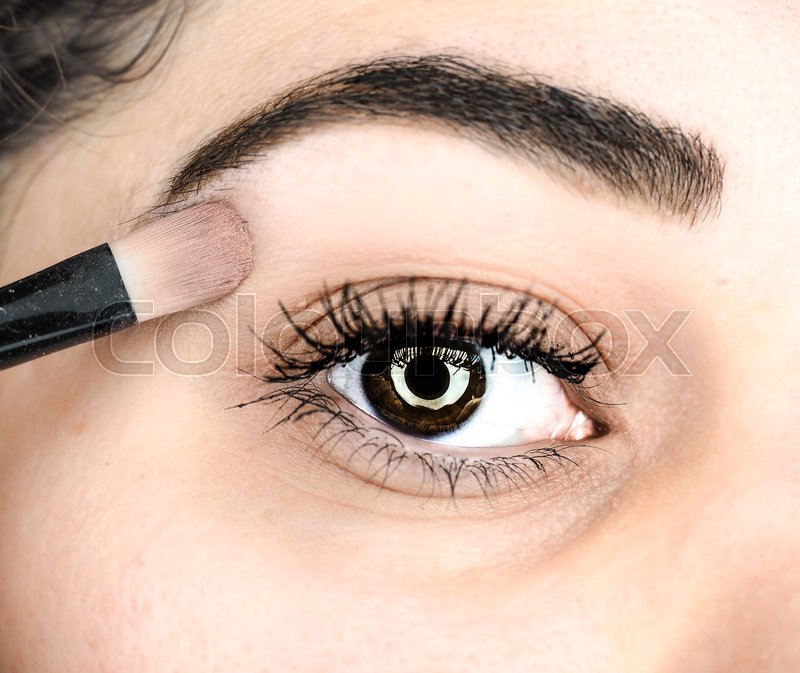 Stock image of 'Female lying final touch of makeup at extreme closeup'