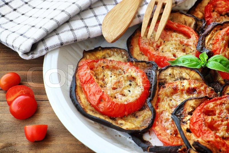 Stock image of 'Tasty Thanksgiving meal, roasted aubergine with tomatoes and cheese on the plate on wooden table, delicious homemade food'