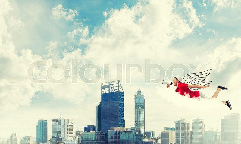 Stock image of 'Young cheerful man with megaphone flying high above city'
